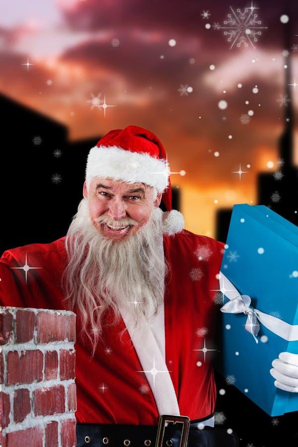 Imagem composta do retrato de Papai Noel que coloca caixas de presente na chaminé fotos de stock