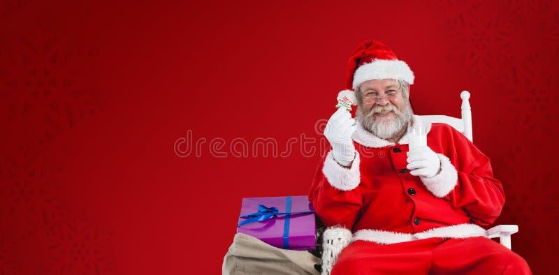 Imagem composta do retrato de Papai Noel que guarda o leite e a cookie foto de stock