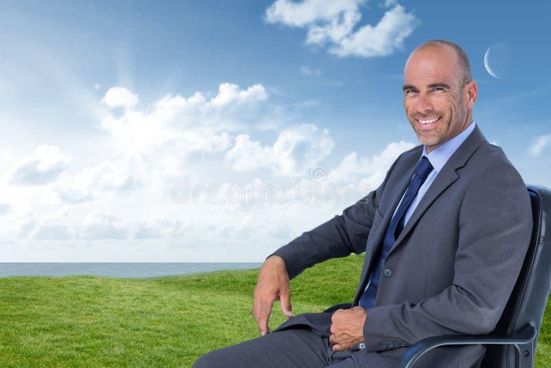 Imagem composta do retrato do homem de negócios seguro que senta-se na cadeira imagens de stock
