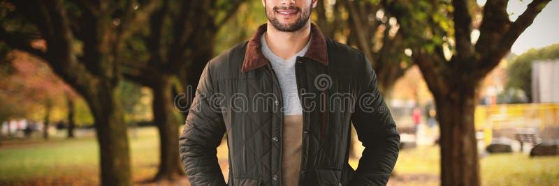 Imagem composta do retrato do homem novo com mãos em uns bolsos que levantam contra o fundo branco imagens de stock royalty free