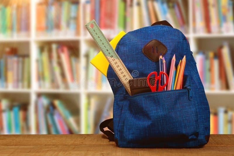 Imagem composta do saco com fontes de escola na tabela de madeira imagens de stock