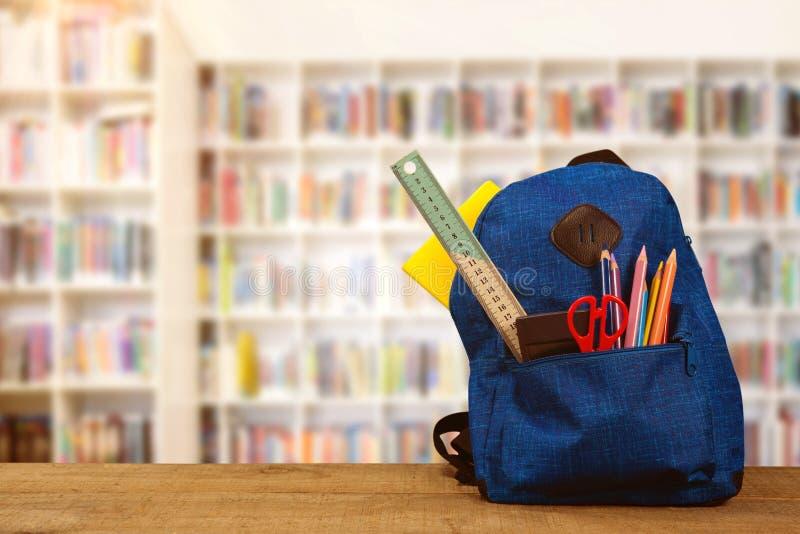 Imagem composta do schoolbag na tabela de madeira ilustração stock