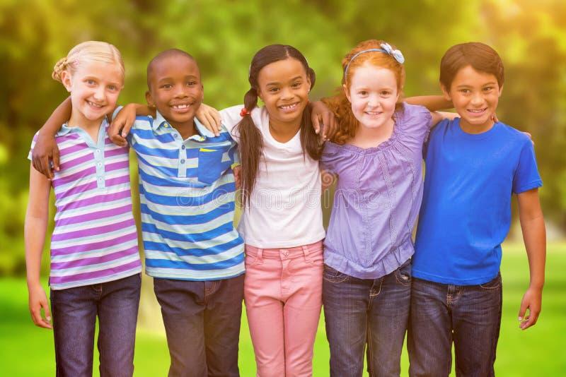 Imagem composta dos alunos bonitos que sorriem na câmera na sala de aula imagem de stock