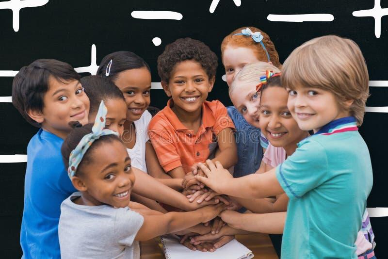 Imagem composta dos alunos bonitos que sorriem na câmera na sala de aula fotografia de stock