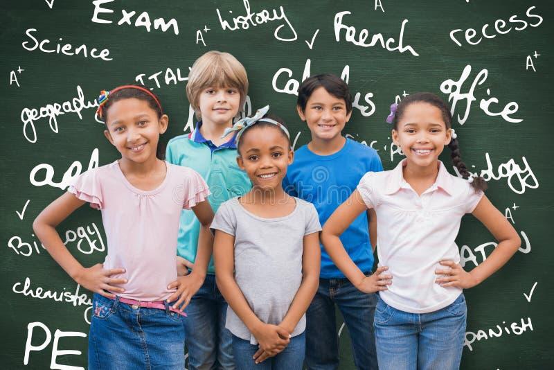 Imagem composta dos alunos bonitos que sorriem na câmera na sala de aula imagem de stock royalty free
