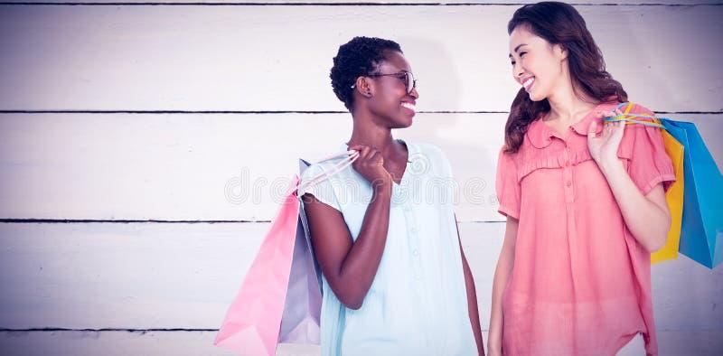 Imagem composta dos amigos fêmeas que guardam sacos de compras foto de stock royalty free