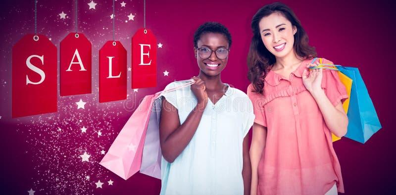 Imagem composta dos amigos fêmeas que guardam sacos de compras imagem de stock royalty free