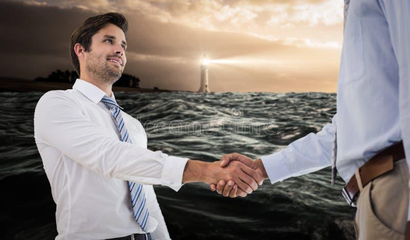 Imagem composta dos homens de negócios novos que agitam as mãos no escritório foto de stock