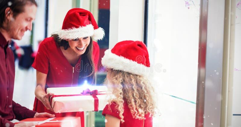Imagem composta dos pais que dão presentes do Natal a sua filha foto de stock royalty free
