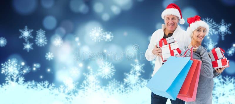 Imagem composta dos pares com sacos de compras e presentes fotografia de stock