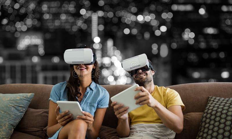 Imagem composta dos pares de sorriso que vestem vidros da realidade virtual ao usar tabuletas digitais no sof imagens de stock