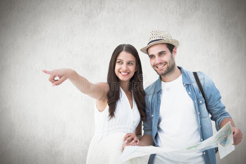 Imagem composta dos pares felizes do moderno que olham o mapa foto de stock royalty free