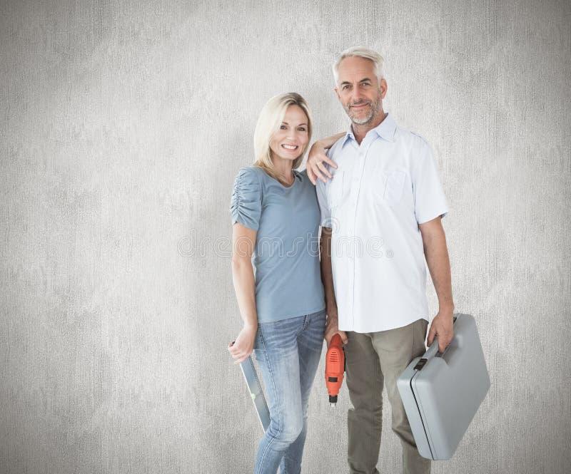Imagem composta dos pares felizes que guardam ferramentas diy imagem de stock royalty free