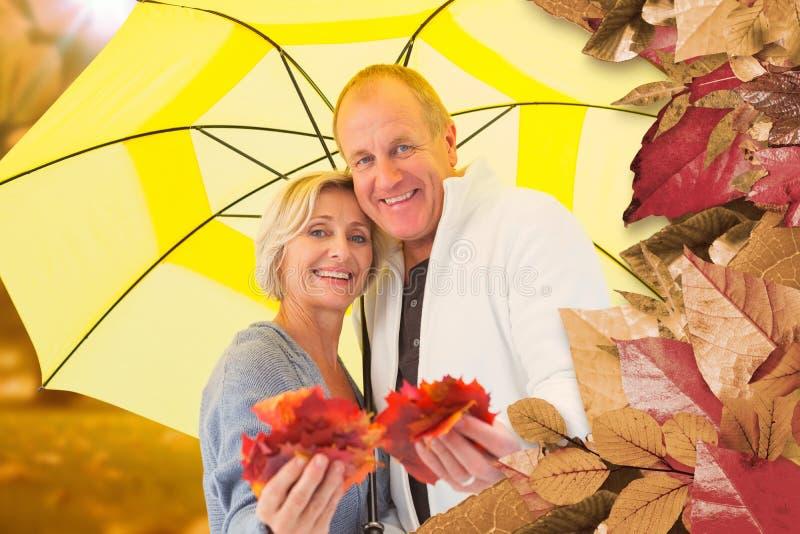 Imagem composta dos pares maduros felizes que mostram as folhas de outono sob o guarda-chuva fotografia de stock
