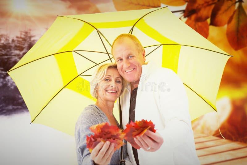 Imagem composta dos pares maduros felizes que mostram as folhas de outono sob o guarda-chuva foto de stock royalty free