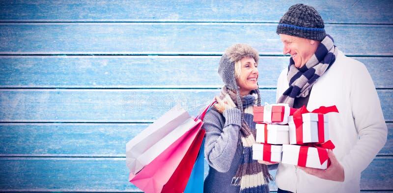 Imagem composta dos pares maduros festivos que guardam presentes do Natal fotos de stock royalty free