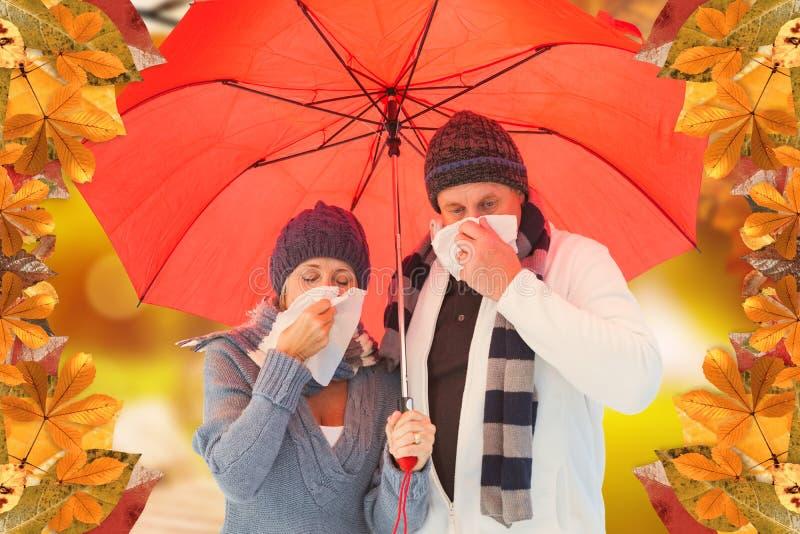 Imagem composta dos pares maduros que fundem seus narizes sob o guarda-chuva imagem de stock