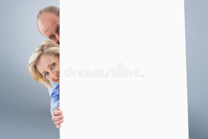 Imagem composta dos pares maduros que sorriem atrás da parede foto de stock royalty free