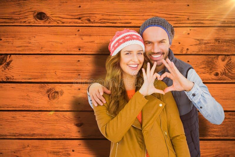 A imagem composta dos pares novos felizes que fazem o coração dá forma com mãos imagens de stock royalty free