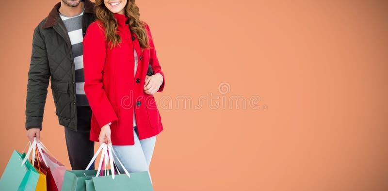 Imagem composta dos pares novos felizes que guardam sacos de compras foto de stock royalty free