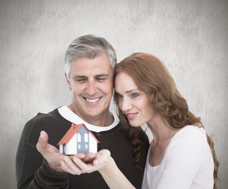 Imagem composta dos pares ocasionais que guardam a casa pequena fotos de stock