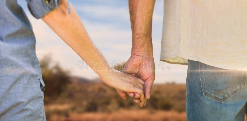 Imagem composta dos pares que guardam as mãos no parque imagens de stock