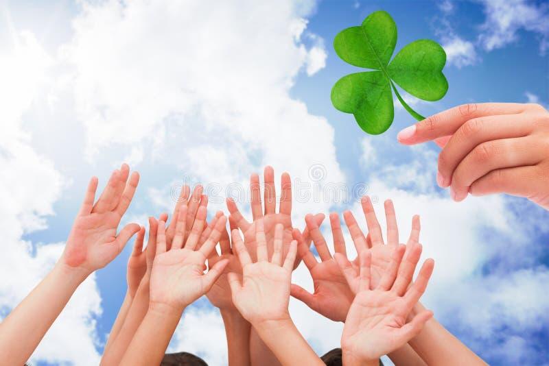 Imagem composta dos povos que levantam as mãos no ar foto de stock