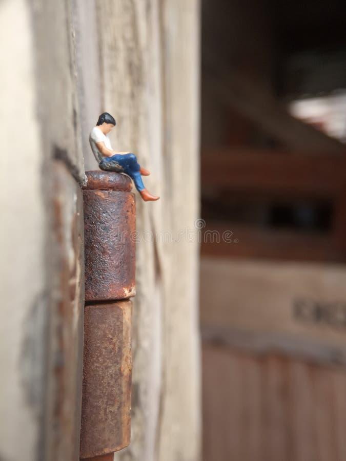 Imagem Conceptual Close Up Foto, Gagdet Addicted Young Man, Segurando Smartphone, sentado na dobradiça corrosiva da porta, sob ar foto de stock
