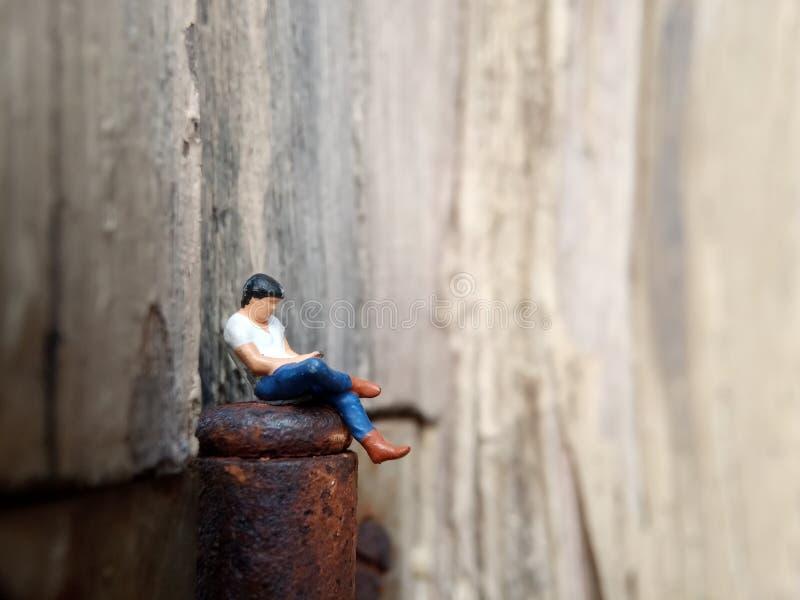 Imagem Conceptual Close Up Foto, Gagdet Addicted Young Man, Segurando Smartphone, sentado na dobradiça corrosiva da porta, sob ar imagem de stock royalty free