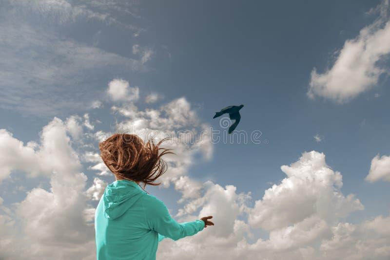 A imagem conceptual da liberdade, uma menina com seu voo do cabelo no vento deixa um pássaro entrar no céu azul imagens de stock