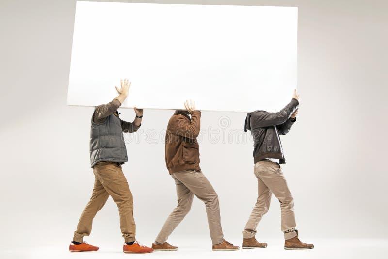 Imagem conceptual de três indivíduos que levam a placa foto de stock royalty free
