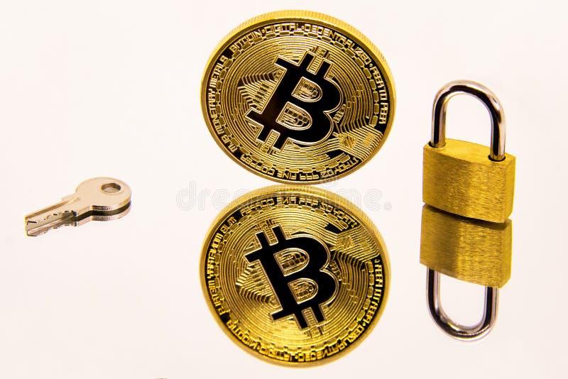Imagem conceptual de uma moeda do bitcoin do cryptocurrency em uma superfície branca do espelho com um cadeado e uma chave dourad imagens de stock royalty free