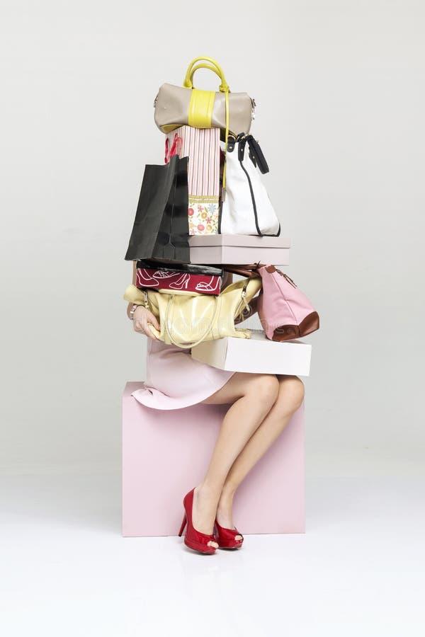 Imagem conceptual de uma mulher que guarda a abundância das bolsas fotografia de stock royalty free