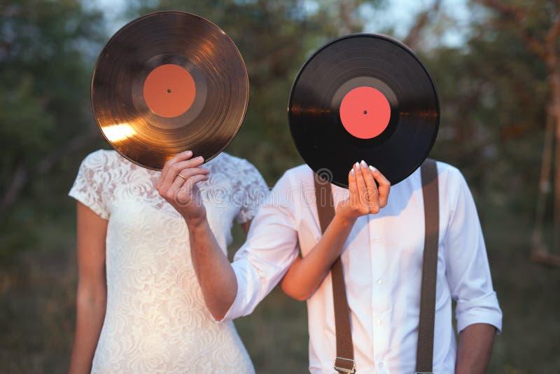 A imagem conceptual do homem e a mulher guardam discos de um registro de vinil em suas caras fotos de stock royalty free