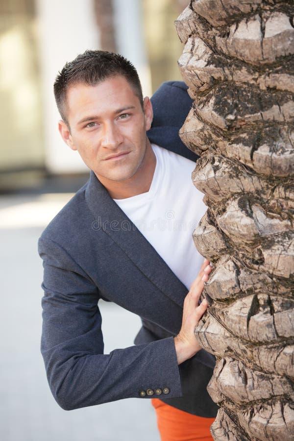 Imagem conservada em estoque de um homem atrás de uma árvore imagens de stock