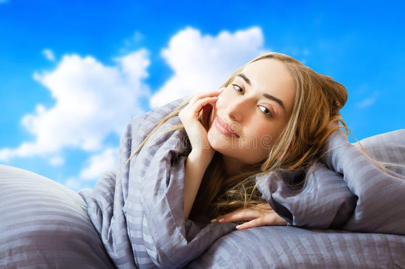 Imagem criativa: Menina na cama depois de dormir no fundo do céu isolada, mulher dormindo, ficar em casa conceito, coronavírus fotos de stock