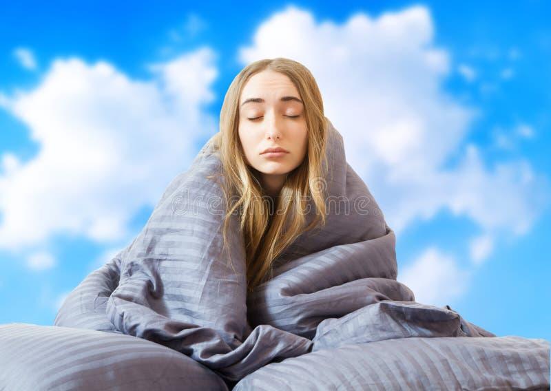 Imagem criativa: Menina na cama depois de dormir no fundo do céu isolada, mulher dormindo, ficar em casa conceito, coronavírus foto de stock
