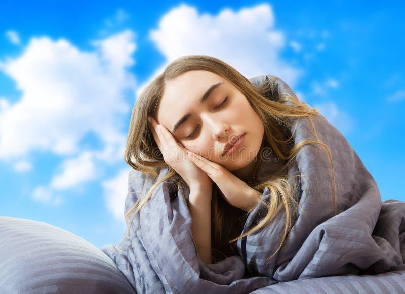 Imagem criativa: Menina na cama depois de dormir no fundo do céu, mulher dormindo, ficar em casa conceito, coronavírus imagens de stock