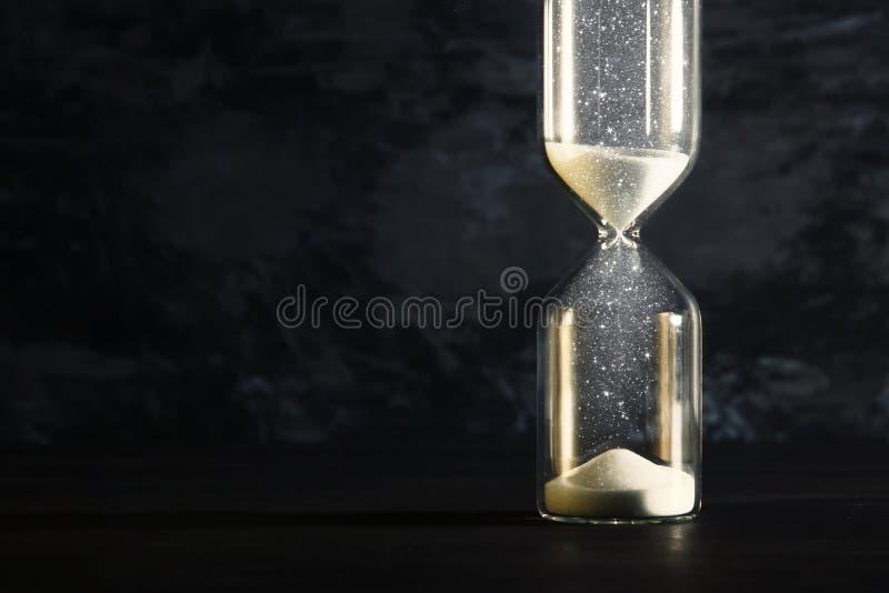 Imagem da ampulheta como a hora que passa o conceito sobre o fundo preto para o fim do prazo do negócio folha de prova do brilho fotografia de stock royalty free