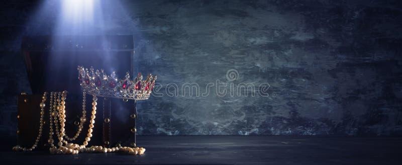 A imagem da arca do tesouro de madeira velha aberta misteriosa com luz e a rainha/rei coroam com as pedras vermelhas dos rubis pe imagens de stock