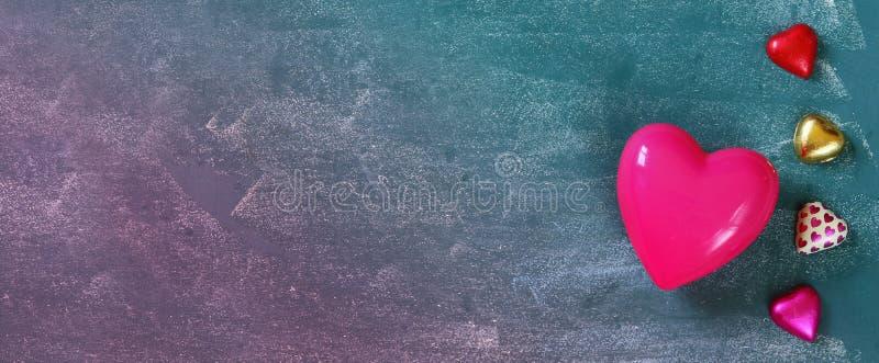 Imagem da bandeira do Web site de chocolates coloridos da forma do coração na tabela de madeira Conceito da celebração do dia de  imagens de stock royalty free