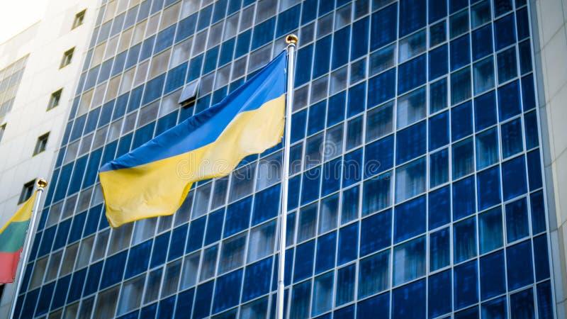 Imagem da bandeira ucraniana amarela e azul contra a constru??o de escrit?rio para neg?cios moderna fotos de stock
