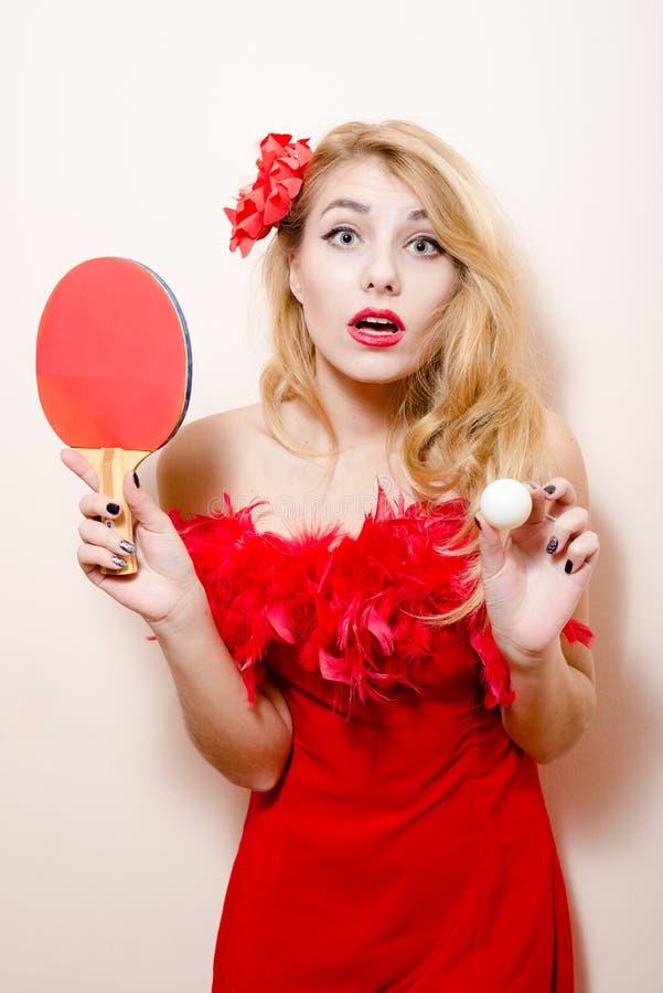 Imagem da bola de bastão do tênis de mesa & da mulher bonita loura da menina bonita elegante do encanto dazedly no vestido vermelh fotos de stock