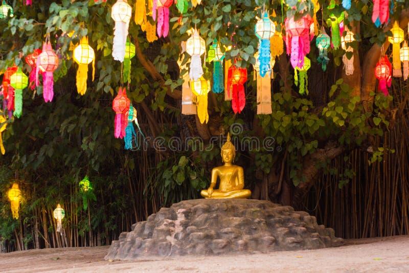 Imagem da Buda sob a árvore budista decorada por lanternas foto de stock