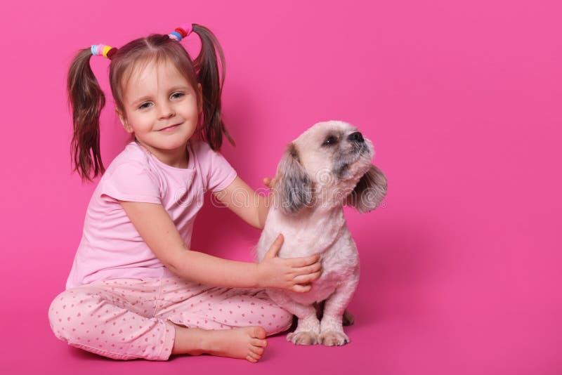 Imagem da criança pequena bonito doce com as duas caudas de pônei engraçadas, estando no bom humor, passando o tempo livre com o  imagens de stock