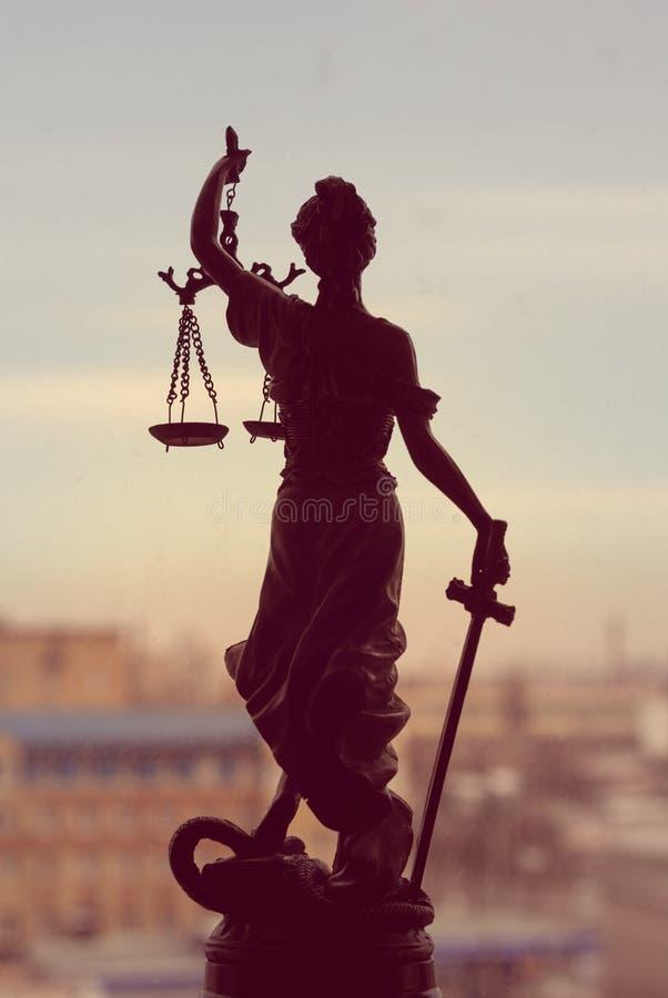 Imagem da deusa Themis ou senhora Justice que está na janela que guarda a venda da espada no fundo da cidade fora imagem de stock