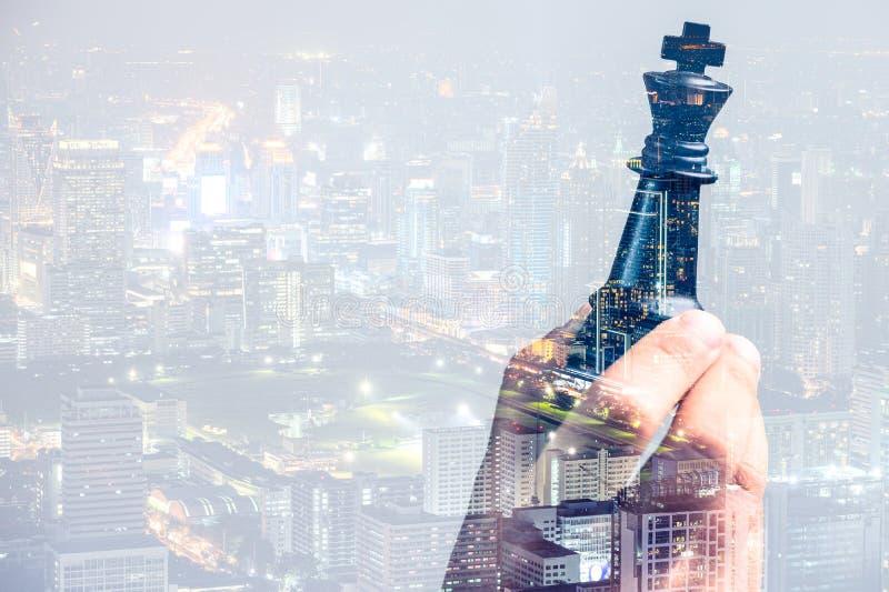 A imagem da exposição dobro da menina mantém um rei da xadrez disponível coberto com a imagem da arquitetura da cidade o conceito foto de stock