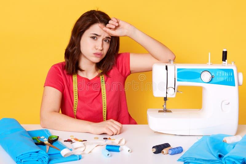 A imagem da fêmea moreno bonita senta-se na mesa de trabalho com máquina de costura, nedles, linha, mantém a mão em sua testa, se fotos de stock