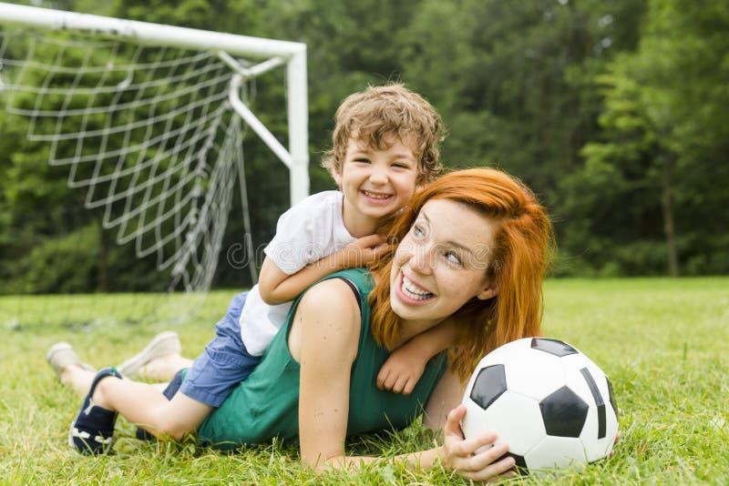 Imagem da família, da mãe e do filho jogando a bola no parque imagens de stock