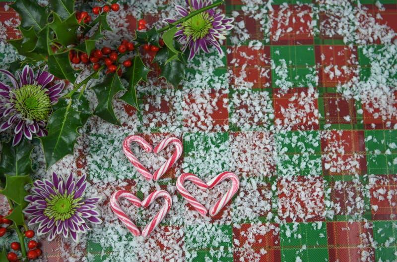 Imagem da fotografia do Natal com os bastões de doces vermelhos da listra na forma do amor do coração com azevinho real e as baga imagem de stock